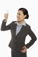 Businesswoman smiling and holding up a light bulb
