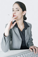 Businesswoman smoking cigarette while doing her work