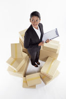Businesswoman standing in the middle of cardboard boxes
