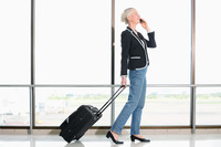 Businesswoman talking on the phone while pulling her luggage