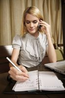 Businesswoman talking on the phone while writing in organizer