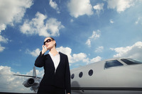 Businesswoman talking on the phone with private jet in the background