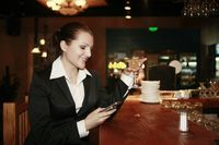 Businesswoman text messaging while holding a glass of cocktail