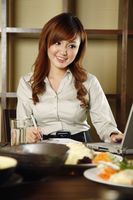 Businesswoman using laptop over lunch at a restaurant