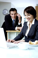 Businesswoman using laptop with her husband talking on the phone in the background