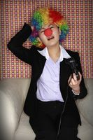 Businesswoman wearing a clown's wig and nose playing video game