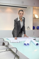 Businesswoman with blueprints on the table