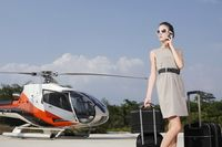 Businesswoman with luggage and briefcase at helipad, talking on the phone