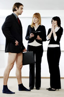 Businesswomen laughing at their colleague for not wearing pants to work