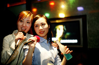Businesswomen singing karaoke after work
