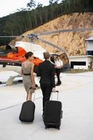Businesswomen walking towards helicopter, pilot waiting for them