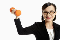 Cheerful businesswoman lifting up dumbbell