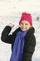 Cheerful girl playing with snowball