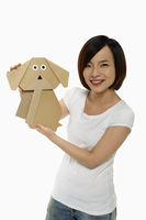 Cheerful woman holding up a paper dog