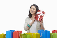 Cheerful woman with a red gift box at her ear
