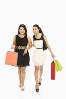 Cheerful women carrying paper bags and smiling