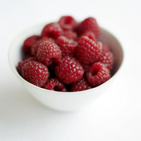 Close up of some raspberries in a bowl