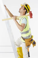 Construction worker climbing up a ladder