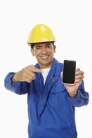 Construction worker holding up a mobile phone