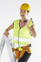 Construction worker standing on ladder, holding a hammer