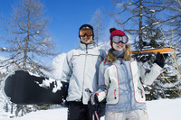 Couple holding winter sport equipments, looking at camera