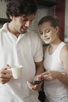 Couple looking at text message while enjoying beverages