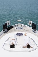 Couple sunbathing on yacht deck
