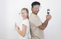 Couple with protection goggles and paint brush posing for the camera