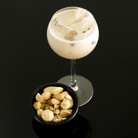 Cream liqueur with ice and bowl of mixed nuts