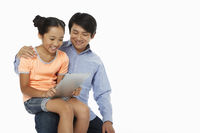 Daughter sitting on father's lap, using digital tablet