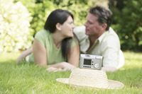 Digital camera on a hat with couple lying forward on the field