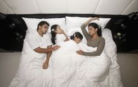 Family sleeping together on bed