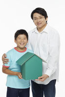 Father and son holding a cardboard house