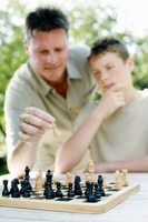 Father and son playing chess game together
