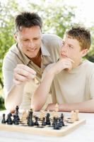 Father and son playing chess game