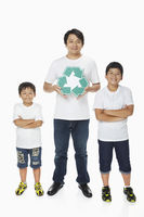 Father holding up a recycle logo while sons stand with arms crossed