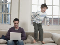 Father using laptop as son jumps on sofa