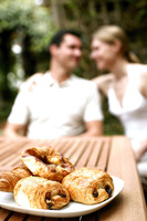 Focus on a plate of croissants with couple sitting in the background