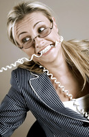 Frustrated businesswoman biting the phone cord