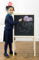 Girl colouring a drawing on chalkboard