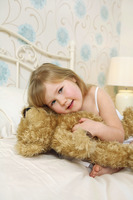 Girl hugging teddy bear on bed