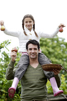 Girl sitting on man's shoulders holding up pears