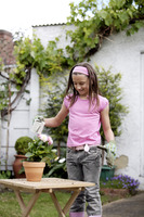 Girl with gardening gloves watering a pot of flowers