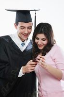 Graduate and woman reading messages on mobile phone