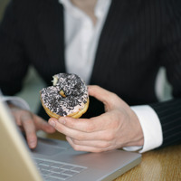 Guy eating doughnut while using laptop