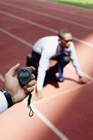 Hand with stopwatch, businessman crouching on starting line in the background