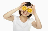 Happy woman covering her eyes with an orange