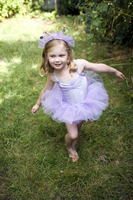 Little girl wearing ballet dress dancing happily