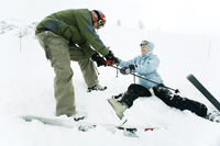 Male skier helping female skier
