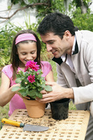 Man and girl planting flower into a pot